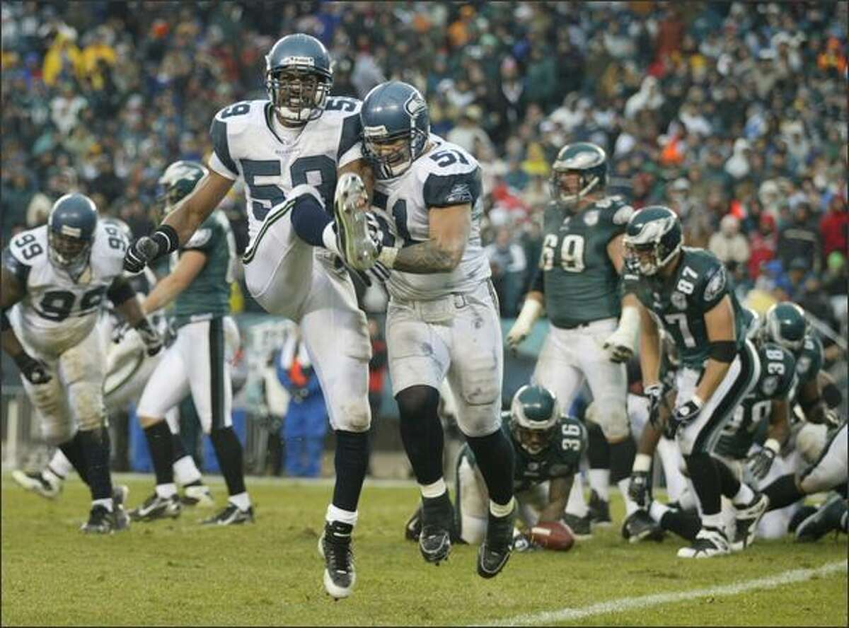 Seattle Seahawks linebacker Julian Peterson and Lofa Tatupu celebrate after the defense stopped Philadelphia Eagles running back Brian Westbrook (in background) on a 4th and goal at the end of the of the 2nd quarter at Lincoln Financial Field in Philadelphia on Sunday, December 2, 2007.