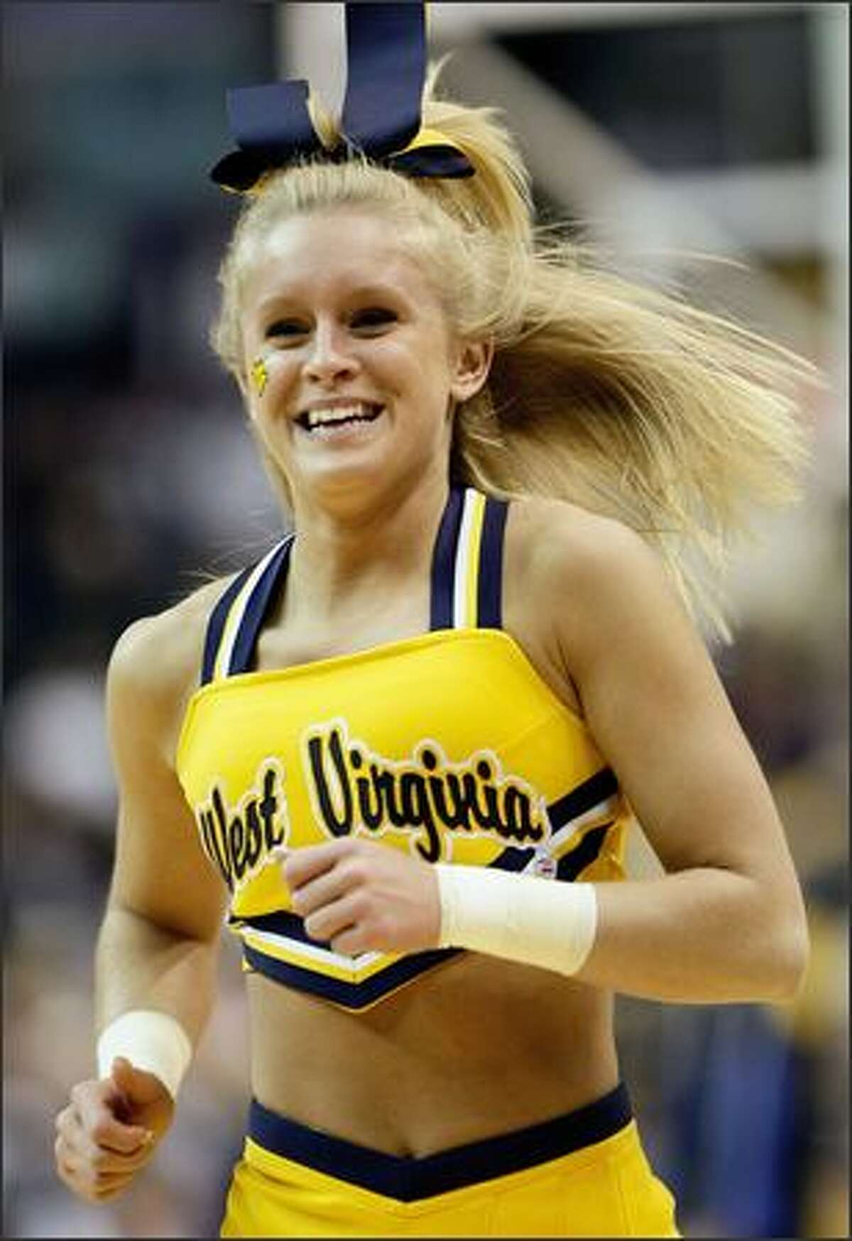 A cheerleader for the West Virginia Mountaineers preforms during a break in play against the Duke Blue Devils during the second round of the West Regional at the Verizon Center in Washington.
