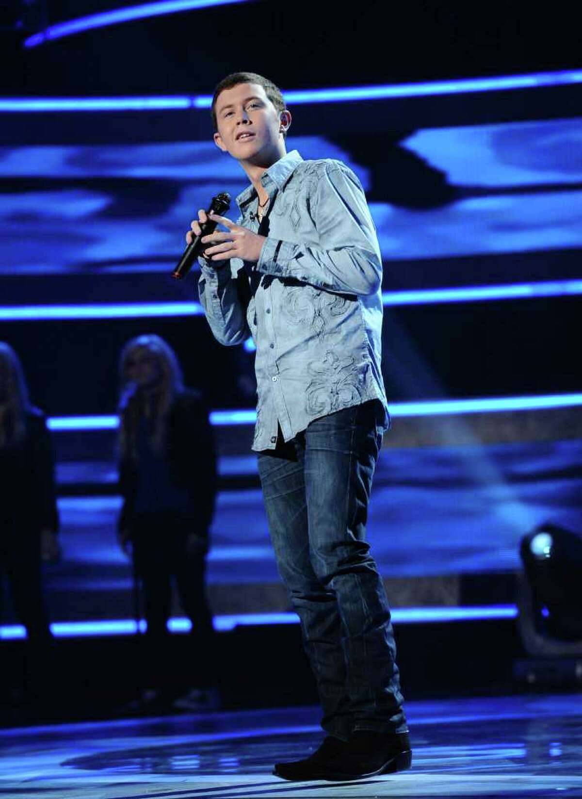 """In this publicity image released by Fox, Scotty McCreery performs on the singing competition series """"American Idol,"""" on Wednesday, March 9, 2011, in Los Angeles."""