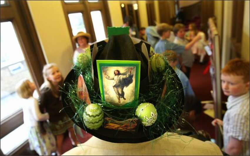 Steve Smith dons a hat inspired by Easter, St. Patrick's Day and Dr. Seuss in the hallway of the church prior to the start of mass.