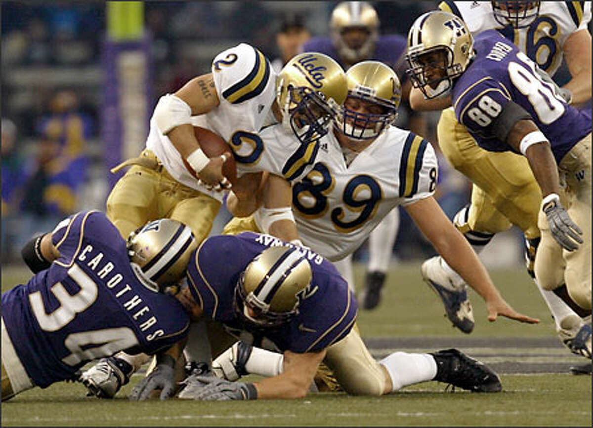 Washington's Greg Carothers (34), Tim Galloway and Marquis Cooper bring down UCLA running back Tyler Ebell (2) in the first half.