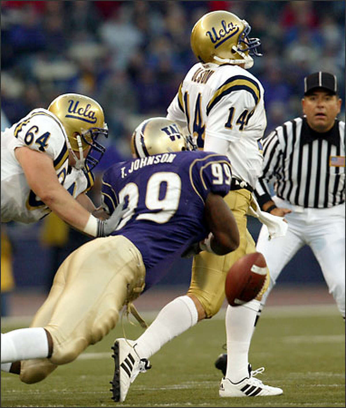 Washington's Terry Johnson (99) strips the ball from UCLA quarterback Drew Olson in the first half, but the Bruins recovered.