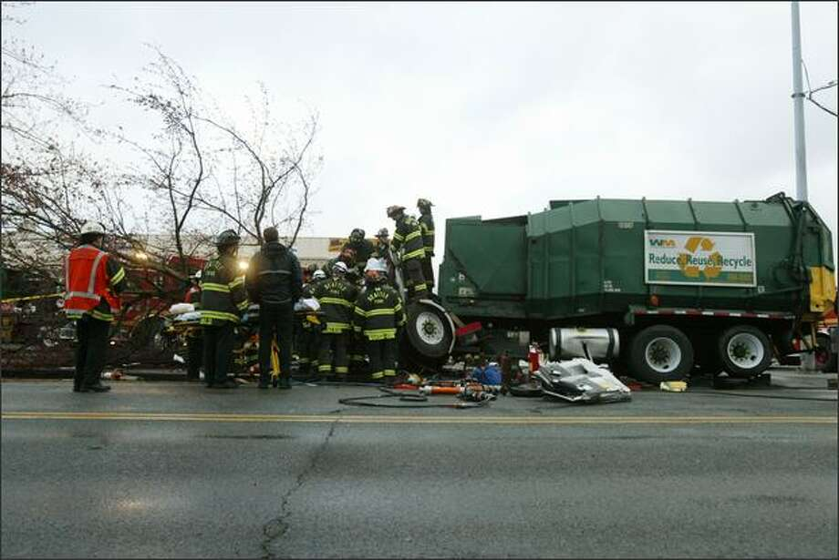 Seattle firefighters work to remove the driver from the wreckage of a garbage truck after he crashed into a tree early Wednesday on North 85th Street, at Palatine Avenue North. The extrication took about 90 minutes because the driver's legs were tangled with the steering column, dash and seat. According to Battalion Chief James Hilliard, the driver was transported to Harborview Medical Center in stable condition with lower leg injuries. Photo: Dan DeLong, Seattle Post-Intelligencer