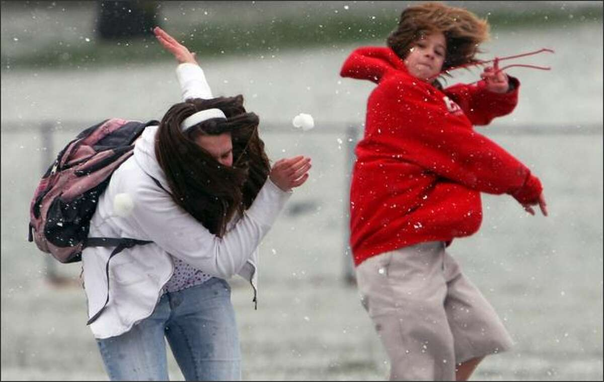 A snowball roars out of the hand of Onesimus Skinner, 12, destined for classmate Gina Rohrbach, 13, at Queen Anne Playfield in Seattle as the friends enjoyed the dusting of white at the park.
