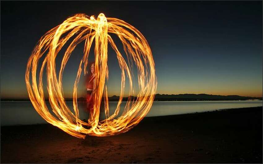 In this 10-second exposure, Sarah Johnson of Seattle spins a cage-like ball of fire as she practices her art at Richmond Beach in Shoreline near Seattle.