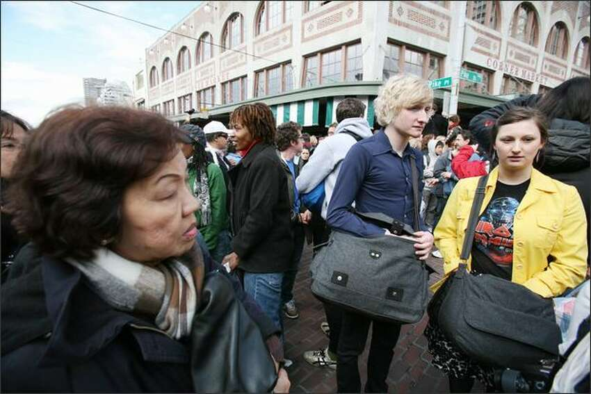 Moments before a flash mob pillow fight began at Pike Place Market on Saturday, people began reaching into their bags for their pillows.