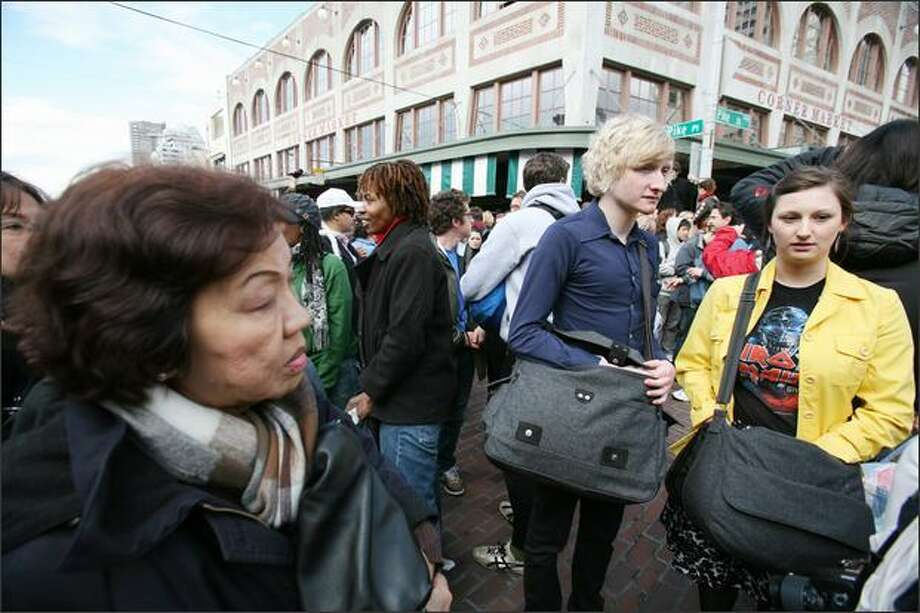 Moments before a flash mob pillow fight began at Pike Place Market on Saturday, people began reaching into their bags for their pillows. Photo: Paul Joseph Brown, Seattle Post-Intelligencer