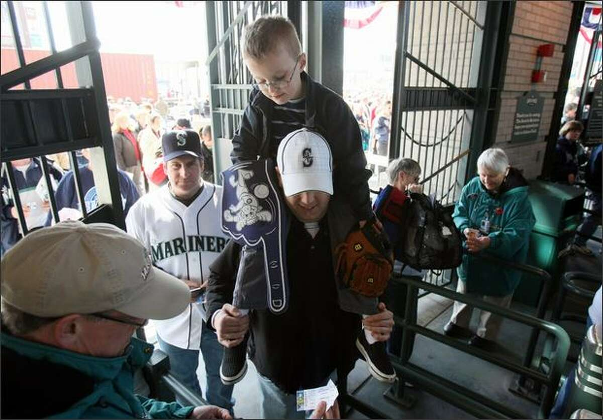 Dana Rolin and his son Stone, 7, of Tacoma, enter Safeco Field during the Mariners season opener. (Photo/Seattle Post-Intelligencer/Joshua Trujillo)