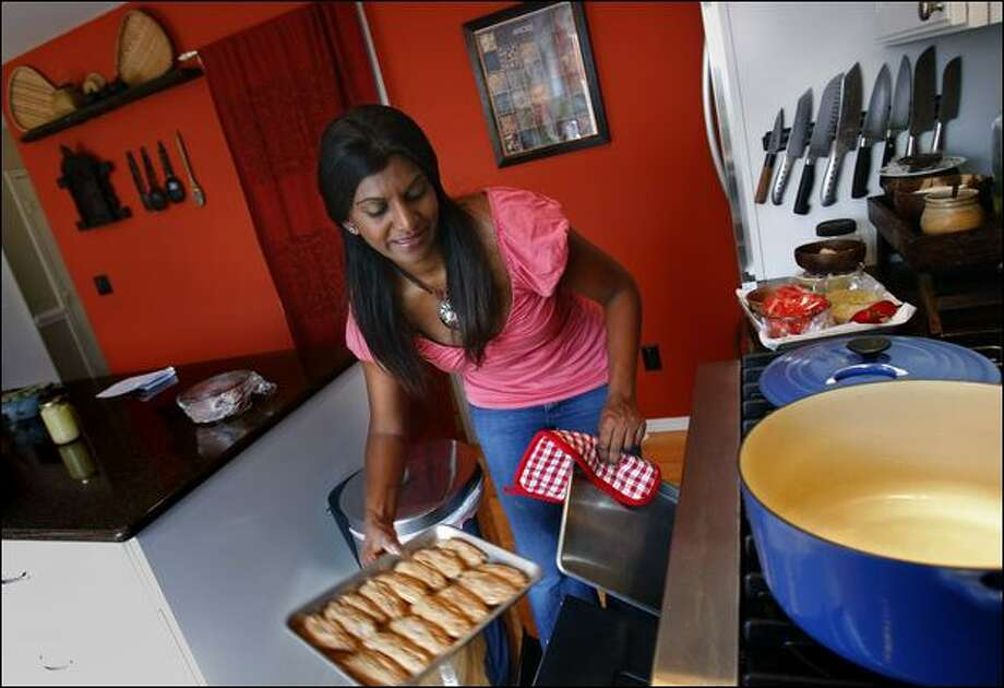 Christina Arokiasamy puts lemon pepper chicken wings in the oven while cooking in her home kitchen in Kent. Photo: Andy Rogers/Seattle Post-Intelligencer