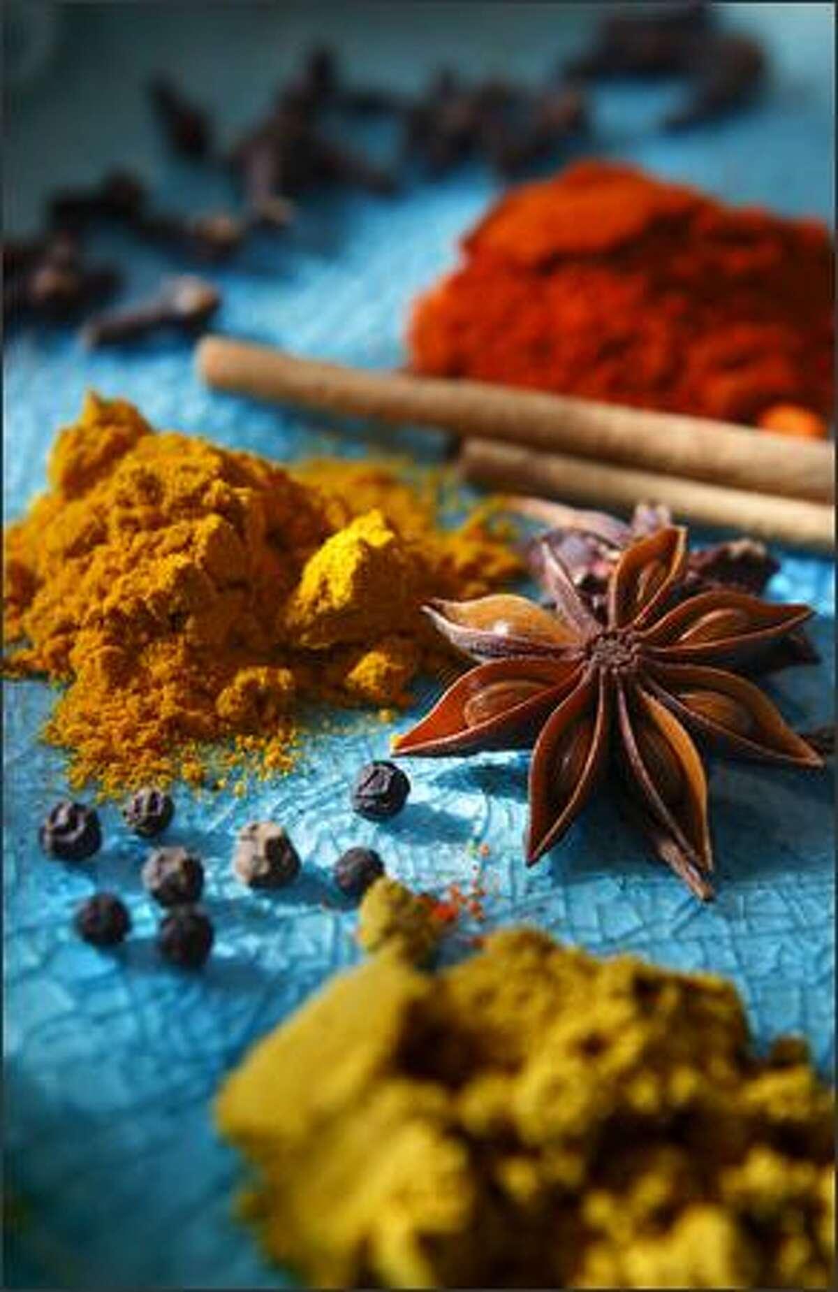 Clockwise from bottom: garam masala, black pepper corns, cumin powder, cloves, turmeric, cinnamon and star anise.