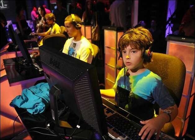 Young gamers play video games at a gaming event this summer in Santa Monica, Calif. On Tuesday, Microsoft said it would co-fund an initiative with several universities in order to find scientific evidence that supports the use of games as a learning tool. Photo: Michael Tullberg/Getty Images