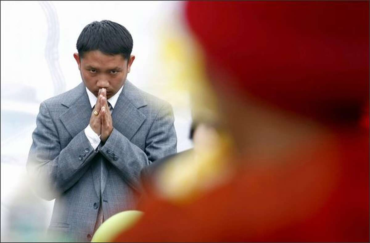Cambodian-American rapper Prach Ly bows his head as a group of monks sing.