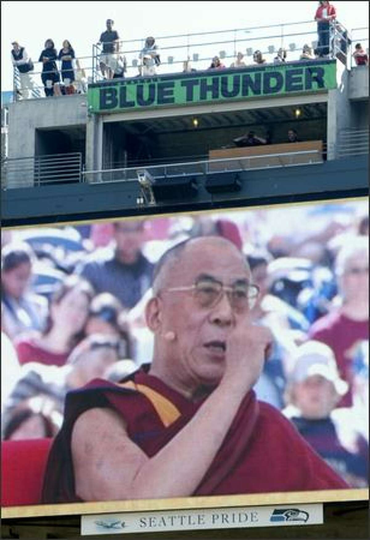 The Dalai Lama is projected on the big screen as he speaks to a Qwest Field crowd about compassion.