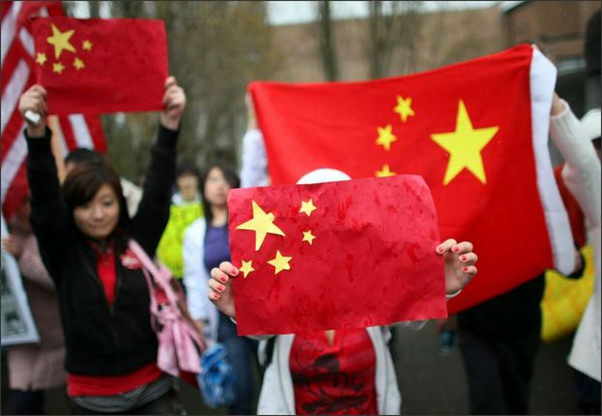 Pro-Chinese protestors show their flag and their disapproval of the Dalai Lama before the religious leader was to receive an honorary degree at the University of Washington.