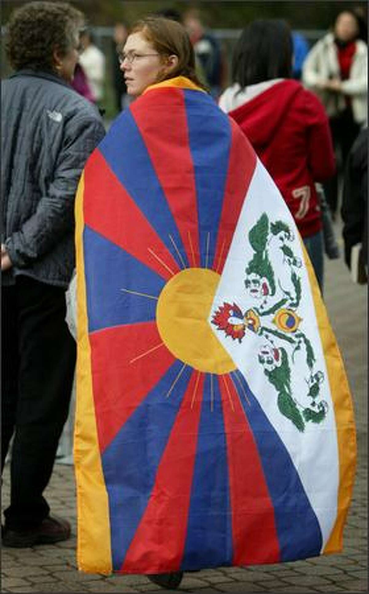 Seattleite Maggie Murdoch, wearing a Tibetan flag, looks back at pro-Chinese government protestors as they show their disapproval of the Dalai Lama before the religious leader was to receive an honorary degree at the University of Washington. Murdoch said she was surprised to see the protestors against the Dalai Lama.