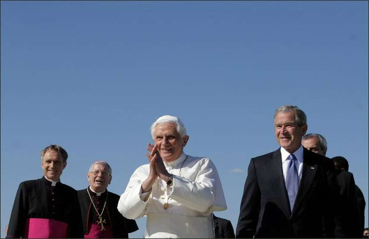 Pope Benedict XVI gestures to the crowd beside US President George W. Bush upon the Pope's arrival at Andrews Air Force Base in Maryland. Pope Benedict begins a six-day visit to the United States, hoping to heal the wounds left in the US church by a decades-long sex scandal, and to tackle other sensitive subjects, including the war in Iraq.