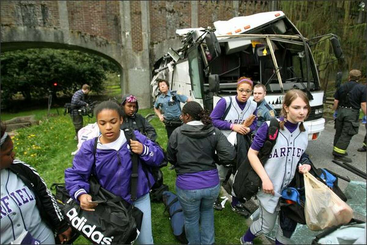 Garfield High School softball players gather their things and walk to another bus after their tour bus collided with a pedestrian bridge along Lake Washington Boulevard in the Washington Park Arboretum.