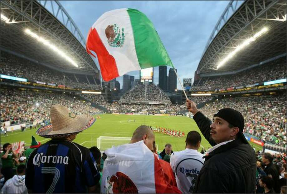 Mario Garcia, right, looks around at the crowd filling the stands of Qwest Field as the Mexican and Chinese national teams are introduced. Orlando Garcia-Almaraz, center, and Juan Gudino, left, joined Garcia. Photo: Joshua Trujillo, Seattlepi.com