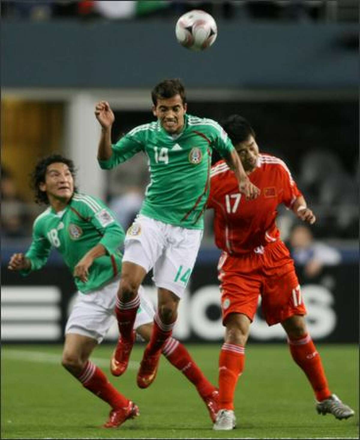 Mexican player Adrian Aldrete (14) heads the ball against Chinese player Sun Ji (17) in the first half of a friendly match between Mexico and China at Qwest Field. At left is Mexican player Cesar Villaluz.