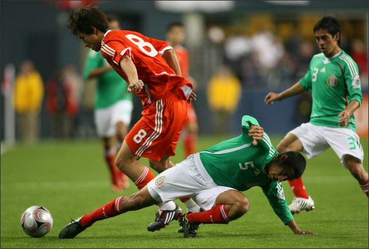 Mexican player Patricio Araujo (5) tries to control the ball against Chinese player Gao Lin (8) in the first half of play at Qwest Field.