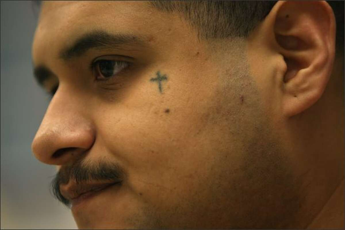 Inmate Rolando Mireles, of Sunnyside, talks to members of the press in a conference room at Clallam Bay Corrections Center. Mireles says the cross tattoo represents his deceased grandmother.