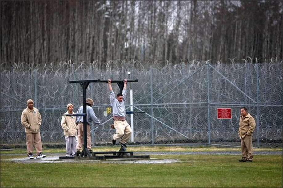 Surrounded by razor wire, inmates exercise in the yard at Clallam Bay Corrections Center. Photo: Mike Kane, Seattle Post-Intelligencer