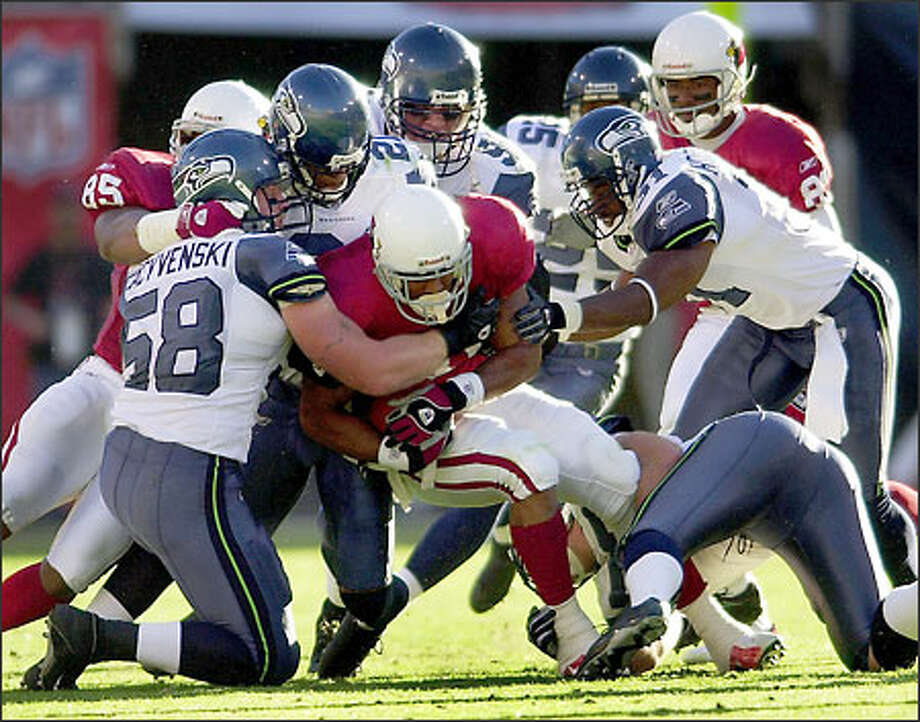 Cardinals running back Marcel Shipp is smothered in a sea of Seahawks as Isaiah Kacyvenski (58), Ken Lucas, second from left, Chad Eaton, third from left, Marcus Robertson, far right, and Marcus Bell, on ground, stop his progress. Photo: Associated Press