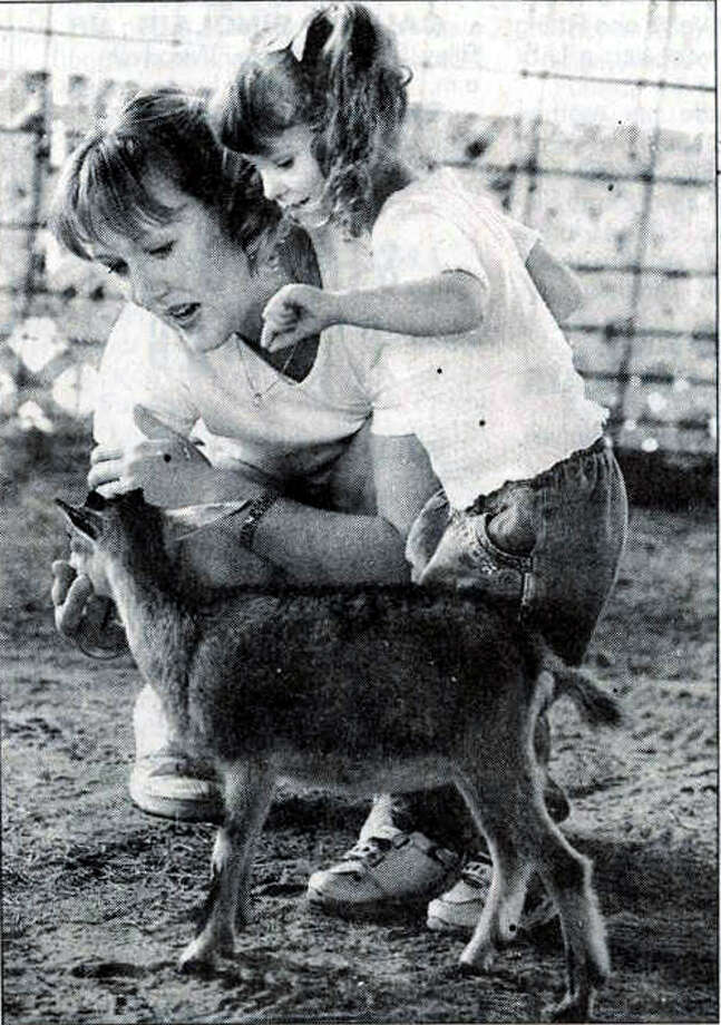 """Emily Ann Swafford, 2, and her mother, Dusty, of Woodville, check out a baby goat at the petting zoo at the South Texas State Fair."" Enterprise file photo 1999"