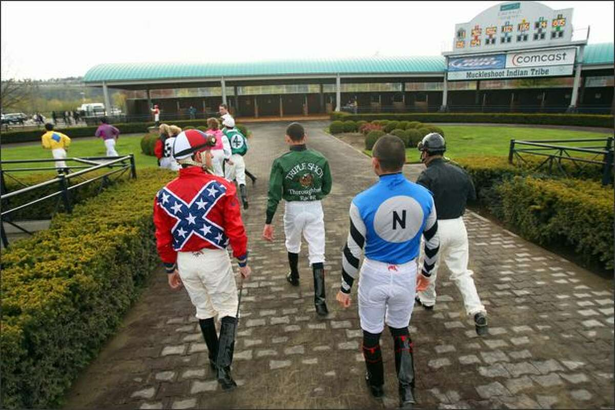 Horse jockeys head back to their locker room after being announced before the start of the first race at Emerald Downs.
