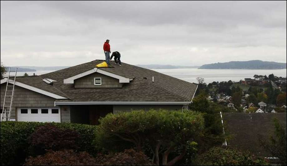 Roofers beging tearing the roof off of the house blocking Dave and Carole Bauman's view of Puget Sound on Wednesday, after a court ordered the roof be flattened. Photo: Brad Vest/Seattle Post-Intelligencer