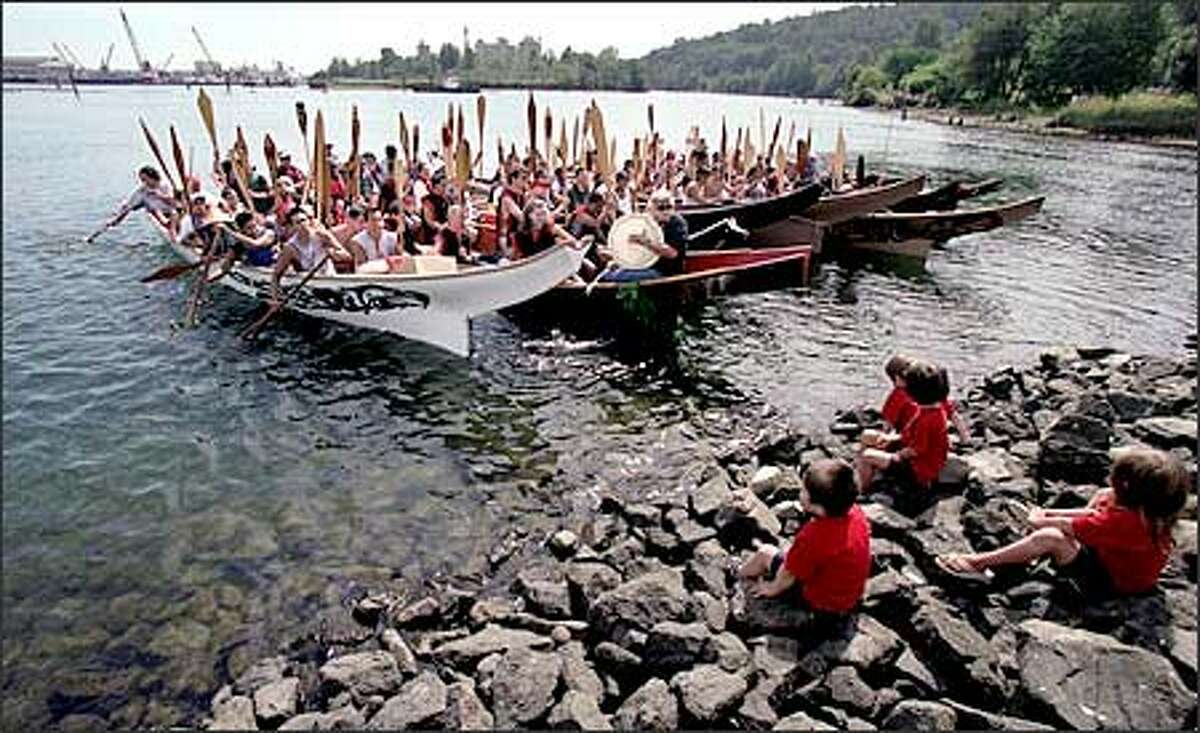 Canoes paddled by members of eight Puget Sound tribes approach the historic site of the Duwamish Tribe's longhouse. The Duwamish River, now a Superfund site, was the source of the tribe's sustenance.