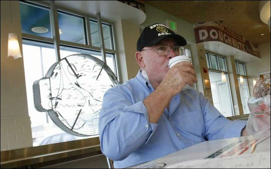 Fontaine Blyle, of Lacey, enjoys a 5-cent cup of coffee at Krispy Kreme on Thursday. Blyle and his wife stopped there on a Seattle visit. Photo: Andy Rogers/Seattle Post-intelligencer Photos