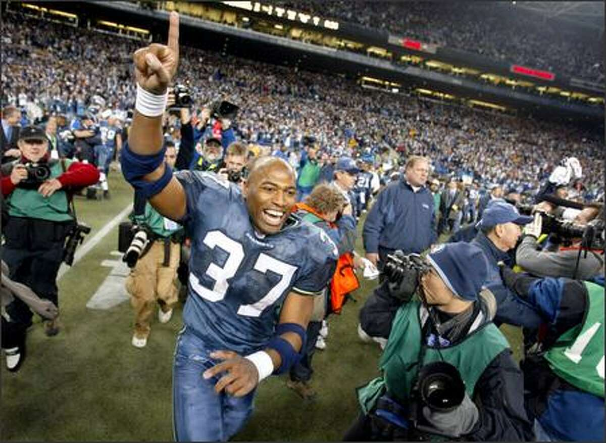 Running back Shaun Alexander runs onto the field to celebrate the Seahawks' NFC Championship victory after time expires.