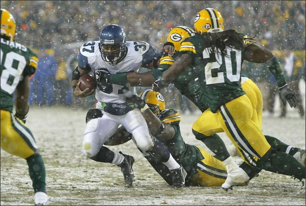 Seahawks running back Shaun Alexander is dropped for a loss of 1 yard by Green Bay defensive tackle Corey Williams in the second quarter.