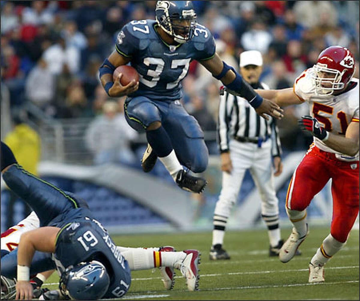 Seahawks running back Shaun Alexander leaps over center Robbie Tobeck, with Chiefs linebacker Scott Fujita in pursuit. Alexander ran for 145 yards.