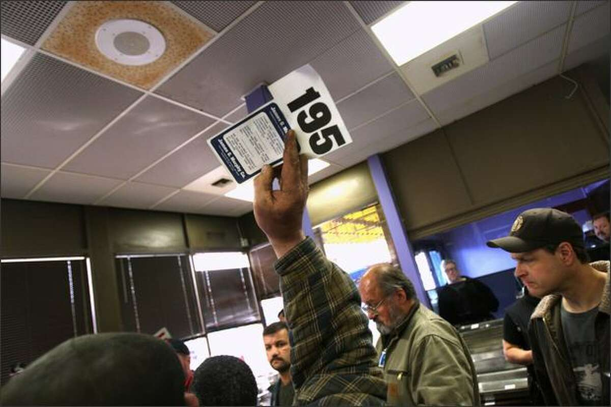 Bargain hunters place bids at Sunset Bowl during an auction put on by James G. Murphy Inc.
