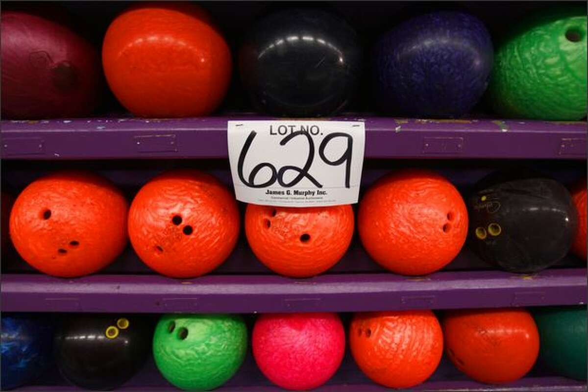 Racks of bowling balls, along with nearly everything else from kitchen equipment to pin setter machinery, is up for sale at Sunset Bowl during an auction put on by James G. Murphy Inc.