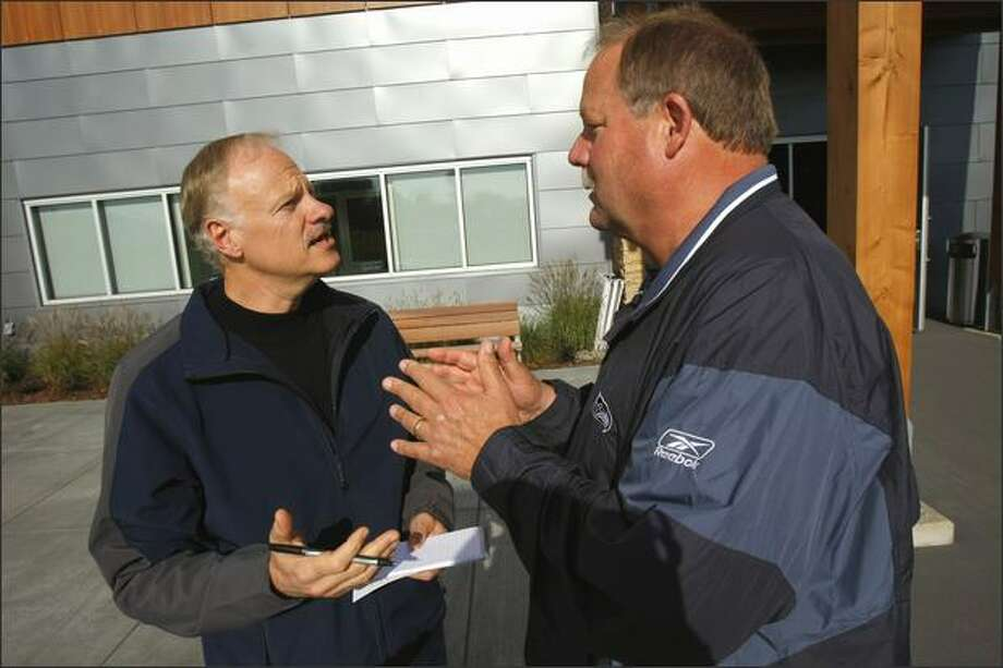 Dave Boling, left, sports columnist for the Tacoma News-Tribune, interviews Seahawks coach Mike Holmgren after a recent practice. Holmgren liked Boling's historical novel so much he passed it along to his wife and daughters. Photo: Andy Rogers/Seattle Post-Intelligencer