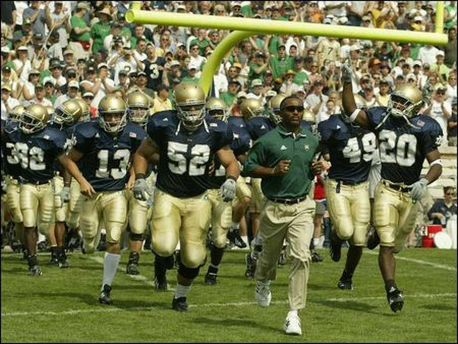 Tyrone Willingham leads Notre Dame onto the field in 2002 -- two years before his firing by the Irish and hiring as Washingon's coach. Photo: Ap File/2002