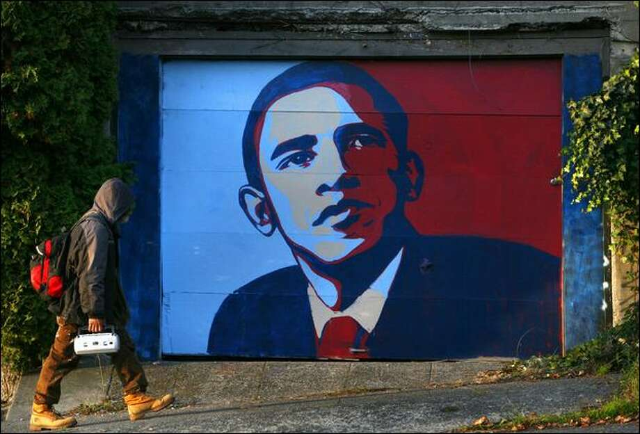 A pedestrian passes Shelly Farnham's garage on East John Street, where Farnham covered graffiti left on the door with an image of Democrat Barack Obama. Photo: Joshua Trujillo/Seattle Post-Intelligencer