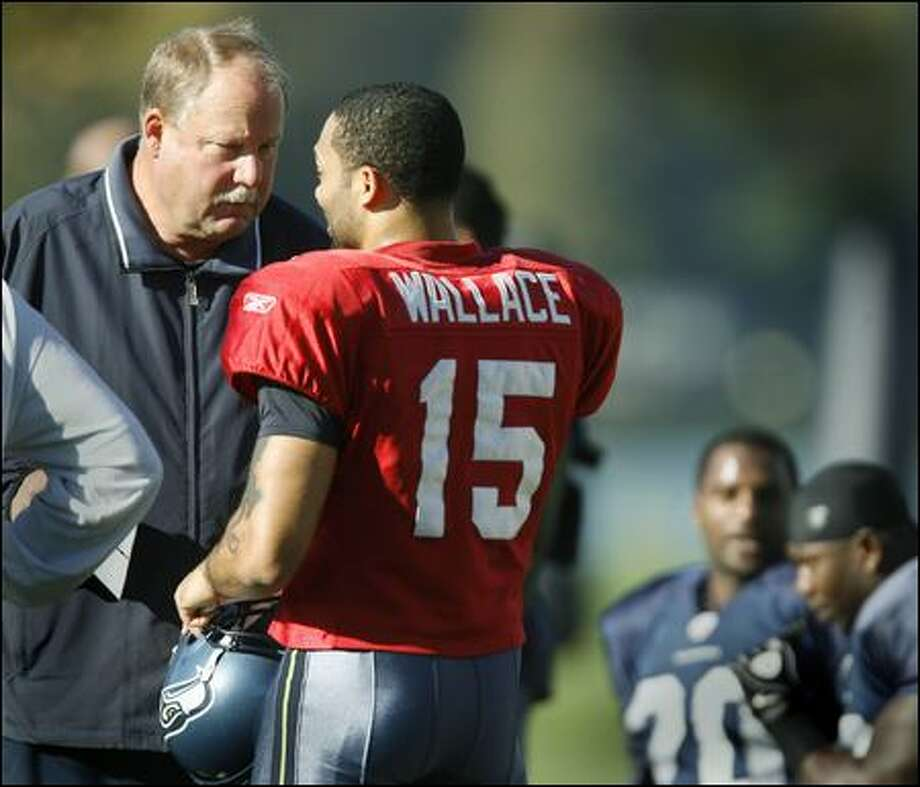 Coach Mike Holmgren speaks with quarterback Seneca Wallace at practice Wednesday, while the injured Matt Hasselbeck continued to get treatment. Photo: Dan DeLong/Seattle Post-Intelligencer