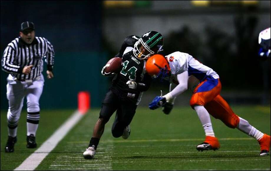 Franklin's Leon Nelson is knocked out of bounds by Rainier Beach's Thomas Williams in the second quarter Thursday at Memorial Stadium. Photo: Joshua Trujillo/P-I