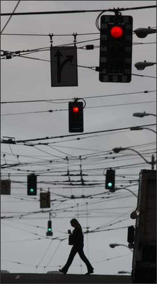 A grid of overhead catenary wires to power buses and strings of traffic lights fill the view looking west on Stewart Street near 4th Ave. in Seattle. Photo: Andy Rogers, Seattle Post-Intelligencer