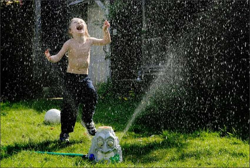 Sharky Munat, who is autistic, plays in a sprinkler outside his Capitol Hill apartment in Seattle last April. Sharky loves to play in water.