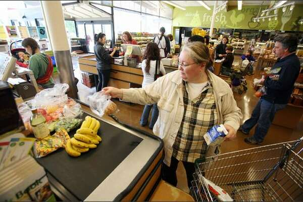 Checking out at the PCC in West Seattle. A single mother without a car, Maggieh Rathbun has to shop frequently because she carries her groceries more than a mile.