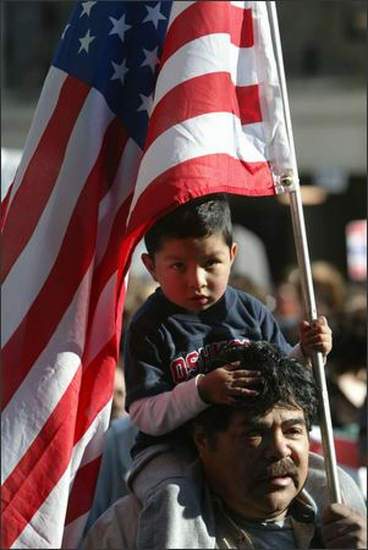 Daniel Cruz 4 holds an American flag sits on his grandpa's, Enrique Lopez, shoulders as they participate in the annual May Day March in downtown Seattle.