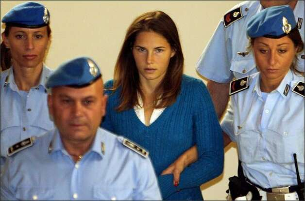 One of the three suspects in the murder of British student Meredith Kercher, Amanda Knox, is escorted by police upon her arrival at a court hearing in Perugia on Sept. 26. Photo: / Getty Images
