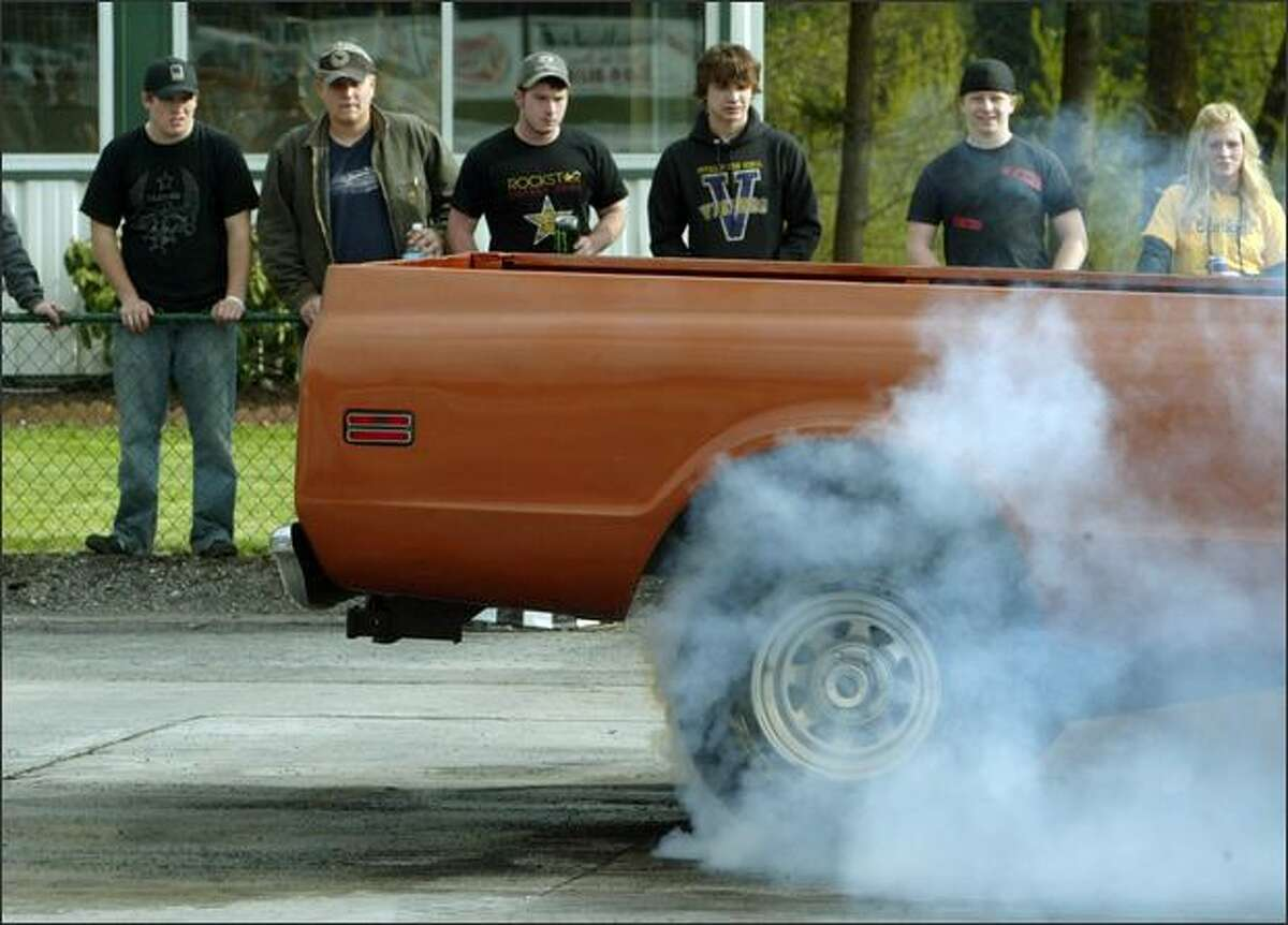 Puyallup High School students (l-r) Aaron McGraw, Colby Caine, Mitchell Shannon, Andrew Rouse, Damon Nash, and Brittan McGlauthlin watch as a driver smokes up his tires at the 2008 Green River Community College High School Drags.