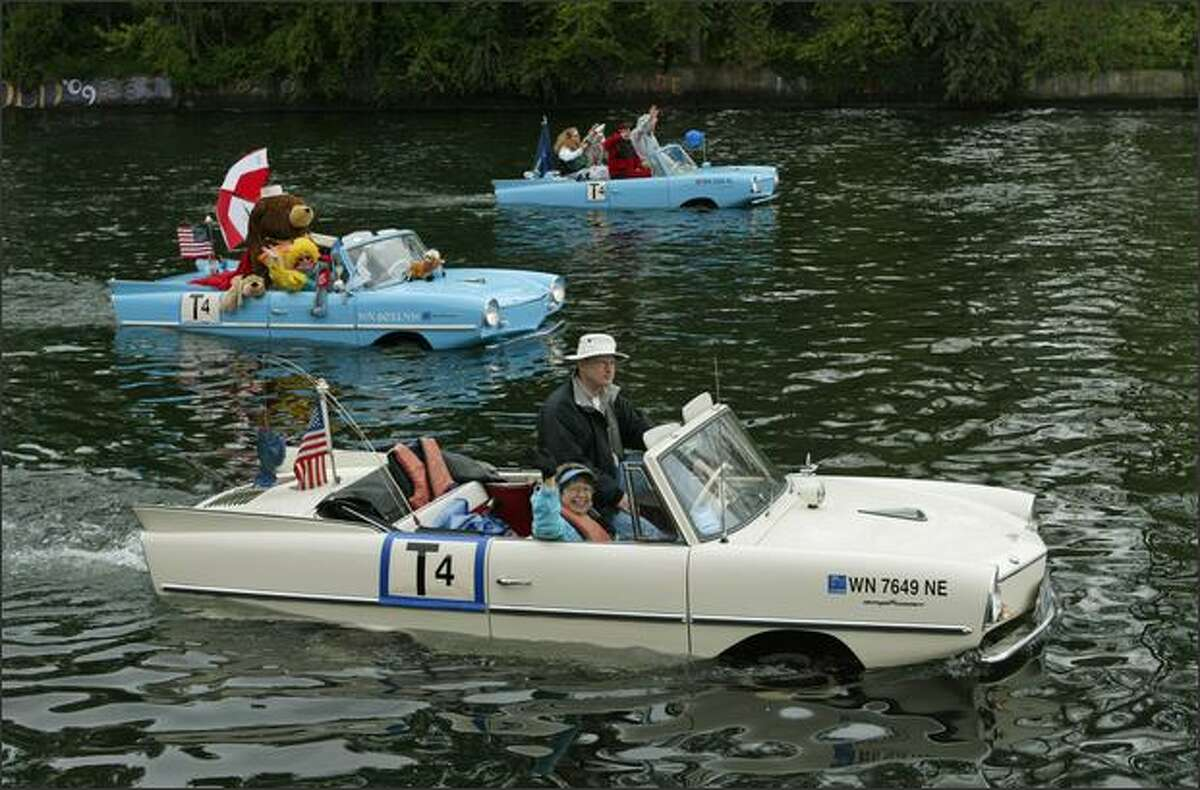 Larry and Nancy Solheim (foreground) wave from their 1966 Amphicar during the Opening Day