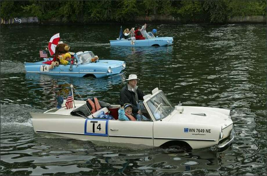 "Larry and Nancy Solheim (foreground) wave from their 1966 Amphicar during the Opening Day ""Parade of Boats"" on the Montlake Cut in Seattle. Photo: Dan DeLong, Seattle Post-Intelligencer"